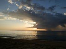 Solnedgång på stranden, havet och molnen Arkivbild