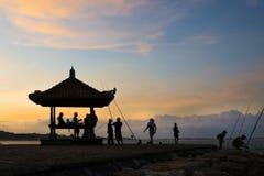 Solnedgång på stranden, konturkoja och några personer fotografering för bildbyråer