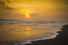 Solnedgång på stranden med att krascha för vågor Royaltyfri Fotografi