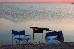 Solnedgång på stranden med BBQ, två fällstolar och ett par av exponeringsglas av öl eller vin Royaltyfria Foton