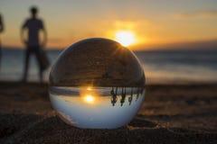 Solnedgång på stranden med den Glass bollen och konturn Arkivfoto