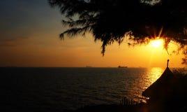Solnedgång på stranden med det gamla skeppet Arkivbild
