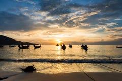 Solnedgång på stranden med fiskebåten i Phuket Arkivbild