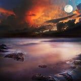 Solnedgång på stranden med sikt till havet och himlen Royaltyfri Bild