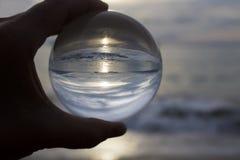 Solnedgång på stranden till och med den glass bollen Arkivbild