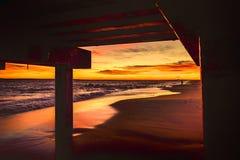 Solnedgång på stranden under en pir Arkivfoton