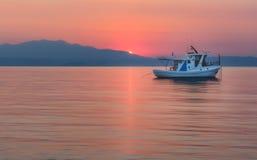 Solnedgång på Thassos och den vita förgrundsyachten arkivbild
