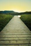 Solnedgång på träpir av laken Banyoles arkivbild
