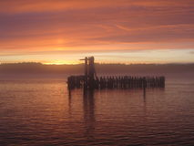Solnedgång på vatten med den gamla pir Royaltyfria Foton