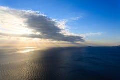 Solnedgång på vattnet dramatisk sky arkivbilder
