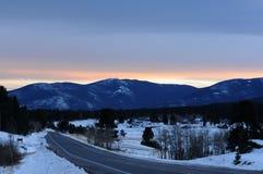 Solnedgång på vinterbergbyn Arkivbild