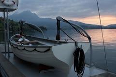 Solnedgång reflekterad i sjövattnet Arkivfoto