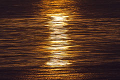 Solnedgång reflekterad på havvågor Arkivbild