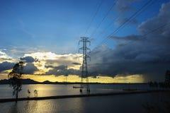 Solnedgång sjöplats med elektriska poler och trådar i söder av Vietnam Royaltyfria Bilder
