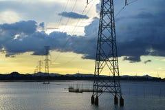 Solnedgång sjöplats med elektriska poler och trådar i söder av Vietnam Arkivbilder