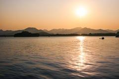 Solnedgång sjösikt Arkivbild
