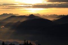Solnedgång/soluppgång i bergen Arkivfoton