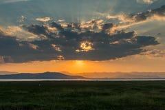 Solnedgång/soluppgång, ljusa strålar med moln royaltyfri bild