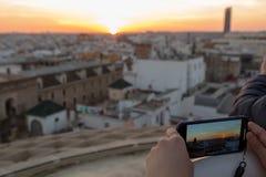 Solnedgång som beskådas på en smartphone i Sevilla arkivfoton