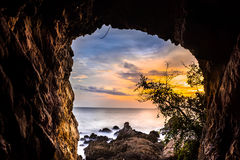 Solnedgång som beskådas till och med en grotta av havet Royaltyfri Foto