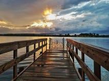 Solnedgång som fiskar skeppsdockan arkivbild