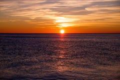 Solnedgång som gjuter lång viktig över havet Arkivbilder