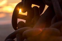Solnedgång som glöder till och med en sammanlänkning av en ankarkedja arkivbilder