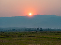 SOLNEDGÅNG som känner sig över skördade risfält Royaltyfria Bilder