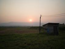 SOLNEDGÅNG som känner sig över skördade risfält Arkivfoton