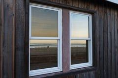 Solnedgång som reflekterar i fönster på den Stillahavs- stranden Royaltyfri Foto