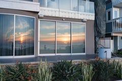 Solnedgång som reflekterar i fönster på den Stillahavs- stranden Fotografering för Bildbyråer