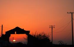 Solnedgång till och med ladugård Arkivbild