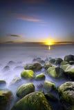 Solnedgång som ses från stenig kust Arkivbilder