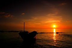 Solnedgång till havet med fiskebåten Arkivfoton