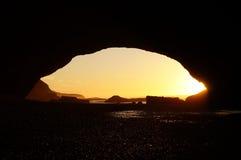 Solnedgång till och med en båge i sandsten Arkivfoton