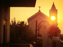 Solnedgång till och med en kyrklig belltower royaltyfri fotografi
