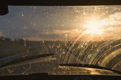 Solnedgång till och med exponeringsglaset av bilen Royaltyfri Fotografi