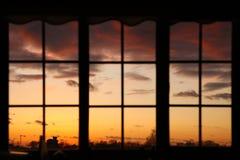 Solnedgång till och med fönster Royaltyfri Foto