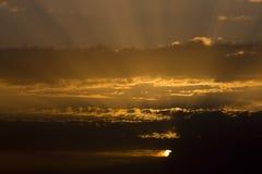 Solnedgång till och med molnen Arkivbilder