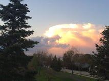 Solnedgång till och med molnen Arkivbild