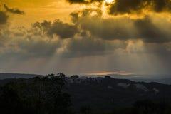 Solnedgång till och med molnen med ljusa strålar royaltyfri fotografi
