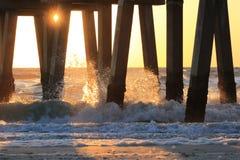 Solnedgång till och med pir Royaltyfri Bild
