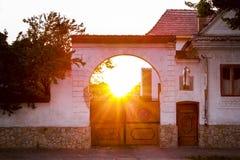 Solnedgång till och med portalen av ett gammalt hus royaltyfri foto