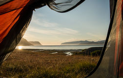 Solnedgång till och med tältdörr Fotografering för Bildbyråer