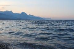 Solnedgång under bergen och havet Arkivbild