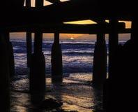 Solnedgång under en pir Arkivbild
