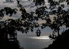 Solnedgång under en vinranka- och lyktakontur med havet royaltyfria foton