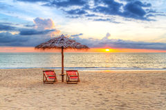 Solnedgång under slags solskydd på stranden Royaltyfria Foton