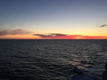 Solnedgång ut i havet arkivfoton