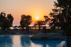 Solnedgång vid havet vid pölen och palmträden arkivfoton